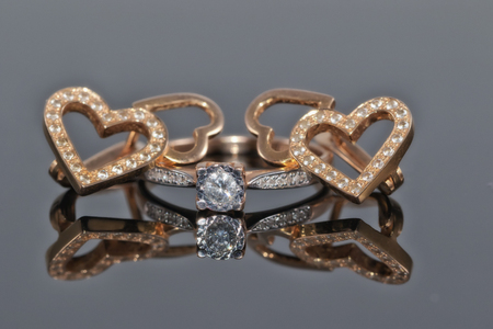 Gold diamond ring and earrings in the shape of a heart with gemstones Standard-Bild