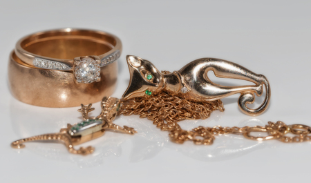 Gold rings, chains, earrings and pendants in the shape of salamanders and cat on a white reflective surface