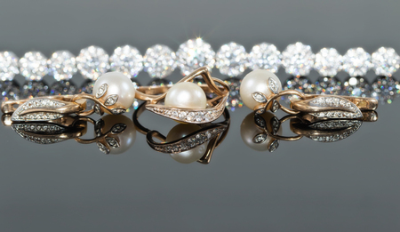 A set of gold jewelry with pearls lies in the background of a silver bracelet with sparkling diamonds Standard-Bild