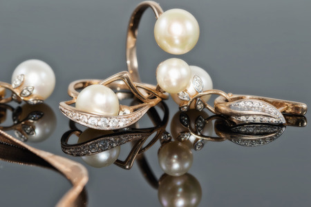 Gift set of gold jewelry with pearls on black reflect surface