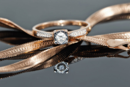 Thin gold diamond ring rests on a chain with a snake weaving Standard-Bild