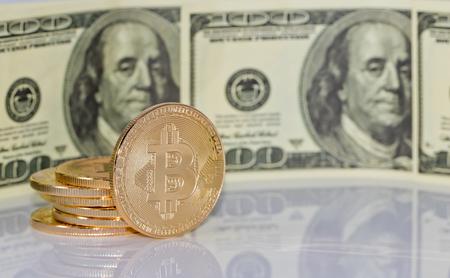 Gold souvenir coin bitcoin and a hundred-dollar bill lying on black reflective surface