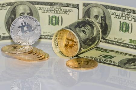 Gold souvenir coin bitcoin and a hundred-dollar bill lying on reflective surface
