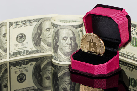 gold souvenir coin bitcoin lies in the gift box for jewelry on the background of dollars