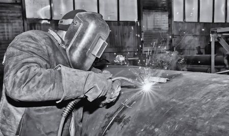 Welding large diameter pipe in workshop conditions by the method of semi-automatic welding in shielding gases. Black and white photo Standard-Bild