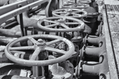 Worn steel catch on the old pipe in the workshop of a refinery with valve. Black and white photo