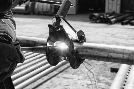 The welder performs Assembly and joining of small diameter pipes with a special centralizer. Black and white photo Standard-Bild