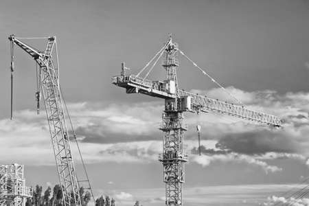 A large tower construction crane involved in the construction of monolithic houses. Black and white photo