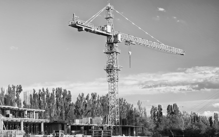 Construction of monolithic apartment house with a tower crane. Black and white photo