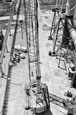 Crawler crane is on site the installation of a petrochemical plant. View top. Black and white photo