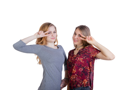 Two beautiful long-haired girls make a gesture of victory hands at the level of the face. Isolated on white background