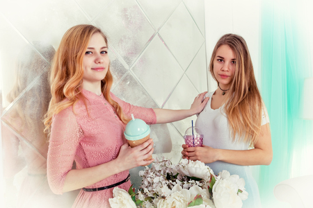 Two cute girls with long hair in dresses drink drinks from cups with lids and tubes Standard-Bild