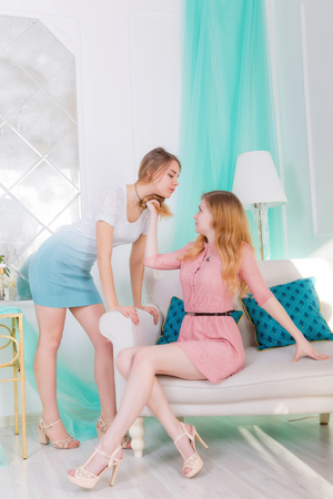 Portrait of two beautiful long-haired girls looking at each other in the fashion interior with sofa and floor lamp Standard-Bild