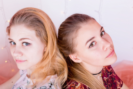 Close-up portrait of two pretty girls sitting in a pose back to back Standard-Bild
