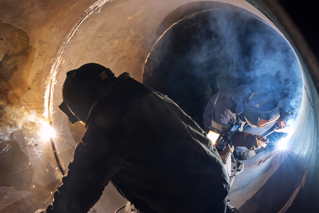 Welding works manual arc welding in the repair of the chemical apparatus by two welders at the same time Stock Photo