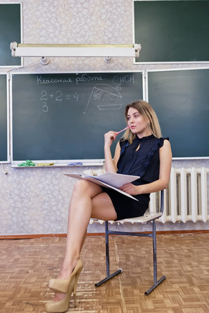 Strict young blonde teacher sits on a chair crossing her legs and dreamy looks at window Stock Photo - 97435412