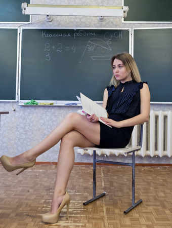 Strict young blonde teacher sits on a chair crossing her legs with a dissatisfied facial expression