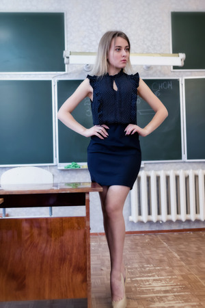 Strict young teacher blonde standing resting her hands on her hips at the blackboard in class and looking at the audience