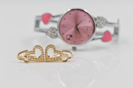 Gold earrings in the shape of a heart and chain with braided snake skin on a background of elegant womens watches