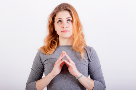 portrait of cute young girl with red hair with folded hands in prayer gesture Stock Photo