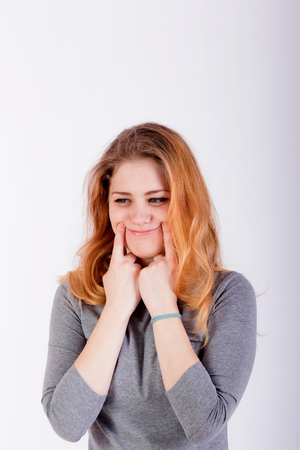 beautiful young woman forcing a smile, holding her fingers near lips, looking with happy expression