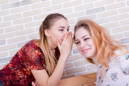 Two beautiful young girls share gossip every whisper in ear