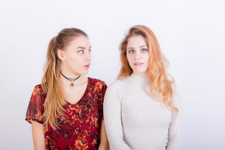 Two young beautiful girls look very surprised after hearing the news Stock Photo
