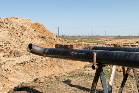 The pipeline Assembly consisting of a pipe and a welded 90 degree outlet lies on the Assembly table of the construction site in an open-air field Stock Photo
