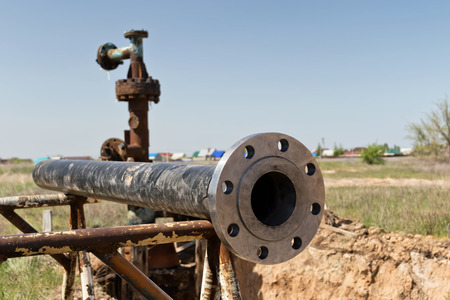 The pipeline Assembly consisting of a pipe and welded flange lies on the Assembly table of the construction site in an open-air field
