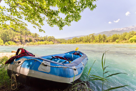 Boot für kollektives Rafting auf einem Gebirgsfluss steht am Ufer mit Rudern und Rettungsausrüstung im Hintergrund der Berglandschaft