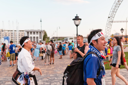 VOLGOGRAD - JUNE 28: Fans of  Japan  national team in branded t-shirts and national flags celebrate team's exit to the stage of playoffs. June 28, 2018 in Volgograd, Russia.