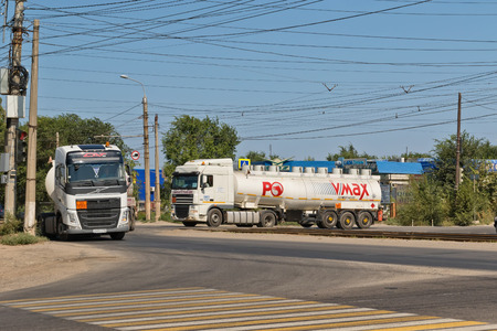 VOLGOGRAD - AUGUST 19: Trucks with white tanks for transportation petroleum products with logo of company Petrol Ofisi ride through industrial area. August 19, 2018 in Volgograd, Russia.