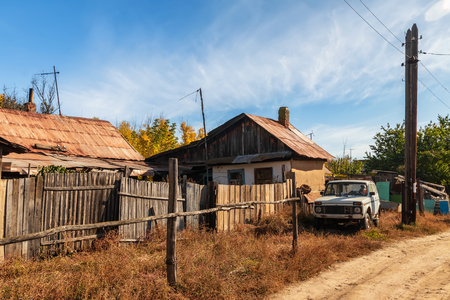 Sketches from the life of a small Russian village. Rickety old wooden fences, small wooden houses and power line poles Standard-Bild - 113035514