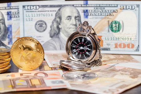 Pocket watches, dollars, euros and bitcoins lie on a wooden table Standard-Bild - 113035604