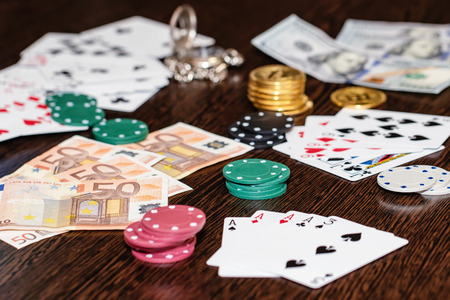 Attributes of gambling on a wooden table - money, cards, playing chips and bitcoins Standard-Bild - 113035608