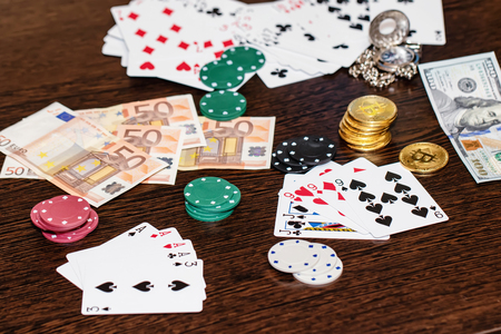 Attributes of gambling on a wooden table - money, cards, playing chips and bitcoins Standard-Bild - 113035663