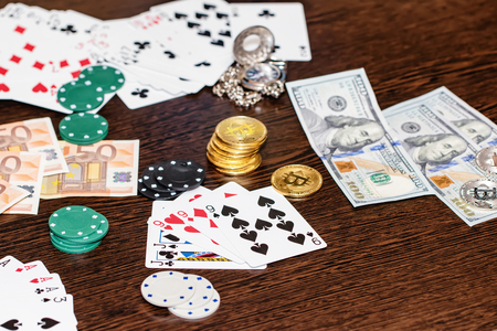 Attributes of gambling on a wooden table - money, cards, playing chips and bitcoins Standard-Bild - 113035664