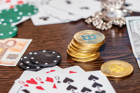 Attributes of gambling on a wooden table - money, cards, playing chips and bitcoins Standard-Bild - 113042271