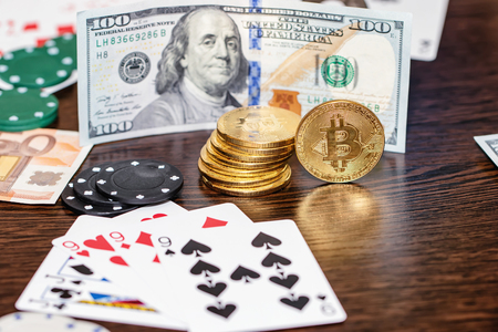 Attributes of gambling on a wooden table - money, cards, playing chips and bitcoins Standard-Bild - 113042272