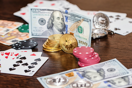 Attributes of gambling on a wooden table - money, cards, playing chips and bitcoins Standard-Bild - 113035665