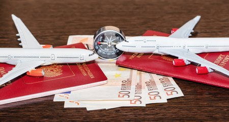 Passports, currency and toy airplanes are on the table Standard-Bild - 113035667