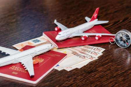 Passports, currency and toy airplanes are on the table Standard-Bild - 113035668