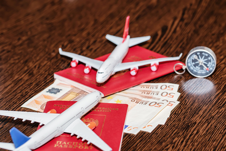Passports, currency and toy airplanes are on the table Standard-Bild - 113035670