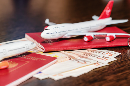 Passports, currency and toy airplanes are on the table Standard-Bild - 113035672
