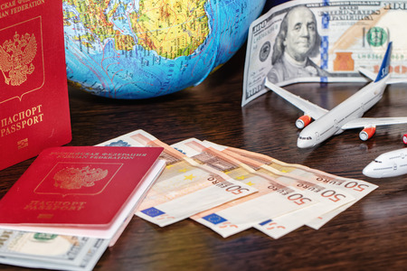 Passports, currency, toy airplanes and a globe are on the table Standard-Bild - 113035673