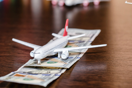 Toy airplane on the runway of hundred dollar bills Standard-Bild - 113035675
