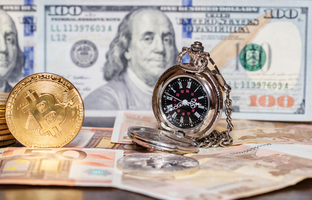 Pocket watches, dollars, euros and bitcoins lie on a wooden table Standard-Bild - 113035680