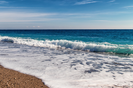 The waves of the Mediterranean sea roll on the pebble beach in clear weather Standard-Bild - 113035681