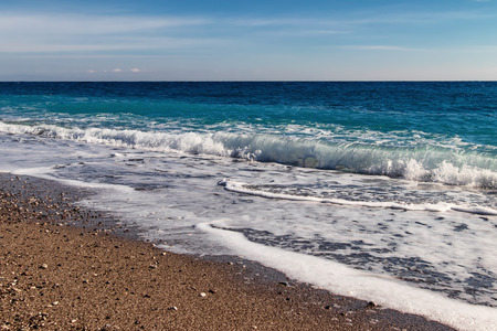 The waves of the Mediterranean sea roll on the pebble beach in clear weather Standard-Bild - 113042273