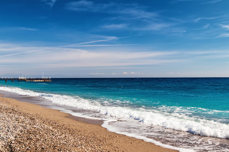 The waves of the Mediterranean sea roll on the pebble beach in clear weather Standard-Bild - 113042274